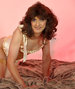 Sexy Crossdresser with a big smile wearing a gorgeous frilly dress and nylon stockings.