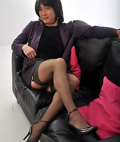 Sexy TGirl in a skirt suite posing on the sofa